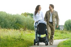 Happy man and woman walking with baby pram outdoors Stock Image
