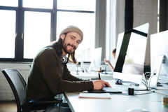 Happy man work in office using computer. Looking at camera. Image of young happy man work in office using computer. Looking at camera royalty free stock image