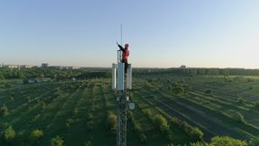 Happy man at work on top of cellular antenna, technician on radio telecommunication tower raises hand with thumb-up on