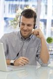 Happy man working at callcenter. Happy young man working at callcenter, using headset, smiling stock photos