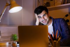 Smiling man wirking with laptop at night at home stock image
