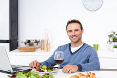 Happy man working on his laptop while having lunch Royalty Free Stock Photos