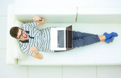 Happy man working on his laptop on the sofa at home Royalty Free Stock Images