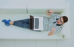 Happy man working on his laptop on the sofa at home. Stock Images