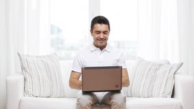 Happy man working with laptop computer at home stock video