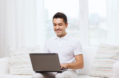 Happy man working with laptop computer at home Stock Image