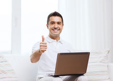 Happy man working with laptop computer at home Royalty Free Stock Photos