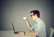 Happy man working on laptop drinking coffee Royalty Free Stock Photos
