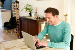 Happy man working on laptop at home Royalty Free Stock Images
