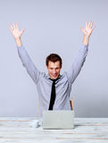 Happy man working on laptop in the office stock photography