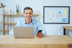 Happy man working in the office. Express positivity. Delighted brunette keeping smile on his face and holding telephone in left hand while looking straight at Royalty Free Stock Images