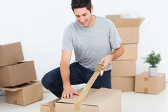 Happy man wrapping a box Royalty Free Stock Photo