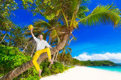 Happy man in yellow trousers and white shirt sitting on a palm t. Ree on a tropical beach and a welcome waving yellow hat. Summer vacation concept Royalty Free Stock Images