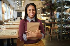 Happy manager in restaurant. Portrait of young attractive mixed race woman standing in wine restaurant with notebook and smiling at camera royalty free stock photos