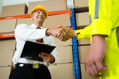 Happy Manager Shaking Hands With Warehouse Worker. Happy Manager Holding Clipboard Shaking Hands With Warehouse Worker Stock Image