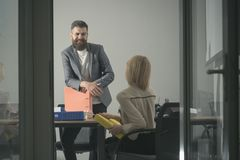Happy manager smile at financier in office. Bearded man and woman discuss financial report. Businessman and. Happy manager smile at financier in office. Bearded royalty free stock photo