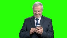 Happy manager typing a message on smartphone. Smiling senior businessman with modern cell phone on green screen stock video