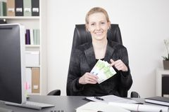 Happy Manageress at her Desk Holding a Fan of Cash Royalty Free Stock Image