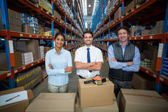 Happy managers are posing in front of cardboard boxes with crossed arms Stock Photo