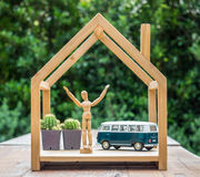 Happy manikin with vintage car model in wooden house Stock Photos