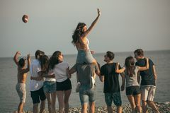 Happy mans and womans walk at the beach Group of friends enjoying beach holidays. Rear view of excited young friends walking on beach. Multiracial group of royalty free stock image