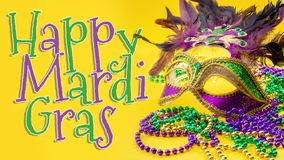 Happy Mardi Gras and Fat Tuesday carnival concept theme with close up on a face mask full of color, feathers and texture and. Golden, green and purple beads royalty free stock photo