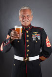 Happy Marine with a Beer. A Happy Marine holds up his beer for a toast Royalty Free Stock Photo