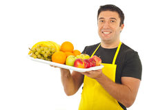 Happy market worker holding fruits. Happy market worker with yellow apron holding fruits isolated on white background Royalty Free Stock Photos
