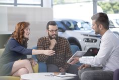 Happy marriage choosing new car while talking with seller in the showroom royalty free stock photography