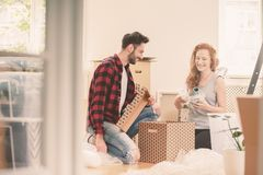 Happy marriage packing stuff into carton box when moving into a new home. Concept stock photo