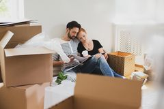 Happy marriage packing stuff into carton boxes while moving-out. Concept stock photos