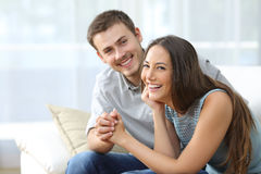 Happy marriage posing at home. Happy marriage posing and looking at you sitting on a sofa in the living room at home Stock Photography