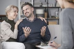 Happy marriage with therapist. Happy, middle-aged marriage during therapeutic session with a therapist Royalty Free Stock Photography