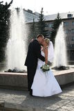 Happy married. The Newlywedses on walk beside fountain. This photo is not correction Royalty Free Stock Photo