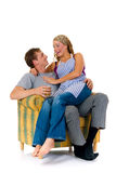 Happy married couple. Two attractive happy youngsters in sofa, happy married couple. Studio, white background Stock Photo
