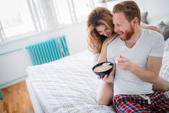 Happy married couple being romantic in bed sharing cereal Royalty Free Stock Image