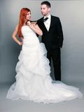 Happy married couple bride groom on gray background. Wedding day. Portrait of happy married couple red haired bride and groom in full length. Woman pulling on Stock Images