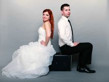 Happy married couple bride groom on gray background. Wedding day. Portrait of happy married couple red haired bride and groom in full length sitting on old Royalty Free Stock Photo