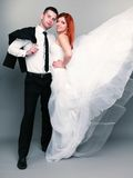 Happy married couple bride groom on gray background Stock Image