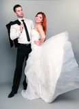 Happy married couple bride groom on gray background Royalty Free Stock Photos
