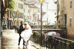 Happy married couple bride and groom running & laughing in old f Stock Image