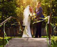 Happy married couple on bridge in sunlight Stock Photos