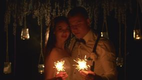 Happy married couple burning bengal lights outdoors. Defocused groom and bride look to eyes each other with love during stock footage