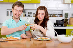 Happy married couple clinking glasses with wine at the kitchen a Royalty Free Stock Photos
