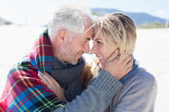 Happy married couple embracing on the beach Stock Images