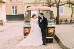 Happy married couple empracing near colorful retro car Royalty Free Stock Images