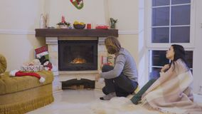 Happy married couple enjoys a fireplace at home. The husband set fire in the fireplace. Young woman observes after him. Handsome man sits near his wife on the stock footage