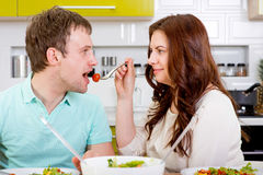 Happy married couple feeding one another with tomatoes Royalty Free Stock Images