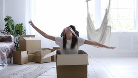 Happy married couple have fun together in new house. Taking a break with unpacking. Girl rides a carton box, her husband. Keeps pushing her. Happy time together stock video footage
