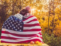 Happy married couple holding the US flag royalty free stock image